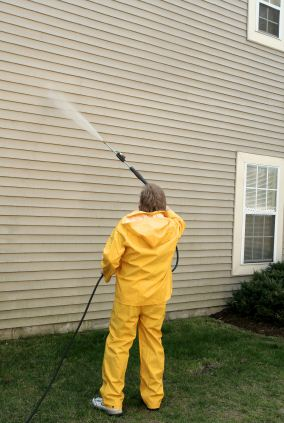 Pressure washing the siding of a house by Yaskara Painting.